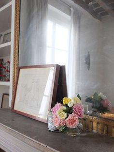 Roses, candle, and a print on a mantel in a 1620s Paris apartment.