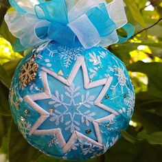 """This handmade quilted ornament """"Snowflake Delight"""", measures 3"""" in diameter and features a sparkling snowflake motif. It is topped with a pretty white and blue bow and snowflake charm."""