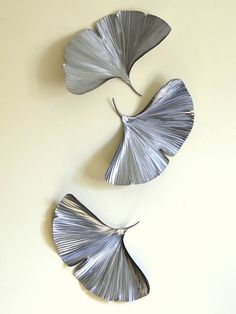 This sculpture captures the beautiful texture and shape of falling gingko leaves.    It is actually 3 separate pieces that can be hung in various arrangements to best fit your space.    Each piece is hand-cut from recycled steel, formed, and textured, then polished and sealed with a satin clearcoat.    There is a sawtooth hanger on the back of each leaf for easy hanging.    Dimensions:  Each leaf is 12H x 20W x 3D.  All 3 leaves as shown in the photo are 40H x 20W x 3D.