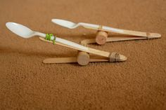 Catapult using plastic spoon, Popsicle sticks, cork,  rubber band. I added a second rubber band near the end of the spoon handle to secure the spoon better. Ask kids to experiment with the placement of the cork to see if they get more or less distance with projectiles. Let's use marshmallows or pom poms for shooting! This is one of the more frugal stick catapult designs I found, using only 2 sticks. Also, there is no gluing, so no wait time betweening making and playing.
