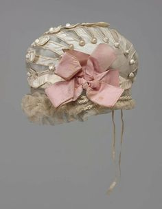 Bonnet, 1800-05 France, the Museum of Fine Arts, Boston    Bonnet. White silk with crossed tabs trimmed with cording over net lining at top; floss-covered buttons at sides and center. Heavier silk band twisted along edge; chenille and floss silk braid and net ruffles at edge. Pink silk ribbon bow on left side. Drawstring at back.