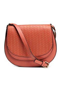 Schoudertas: Een schoudertas van imitatieleer met een metalen beugel. De tas heeft een klep met een geponst vlechtdessin en een magneetsluiting, een verstelbare schouderriem met een metalen gesp en een groot buitenvak achteraan. Gevoerd. Afmetingen 5x16,5x22 cm.