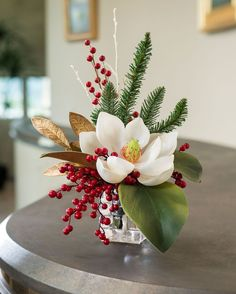 The elegant charm of a single magnolia with thick, lush leaves makes it a favorite flower during the holiday season. Red berries, blue spruce, and gilded laurel complete this welcoming holiday silk tabletop accent arranged in a stylish heavy glass cube.