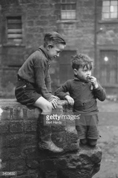 Two young boys from the Gorbals area of Glasgow. The Gorbals tenements were built quickly and cheaply in the 1840s, providing housing for Glasgow's burgeoning population of industrial workers. Conditions were appalling; overcrowding was standard and sewage and water facilities inadequate. The tenements housed about 40,000 people with up to eight family members sharing a single room, 30 residents sharing a toilet and 40 sharing a tap. By the time this photograph was taken 850 tenements had...