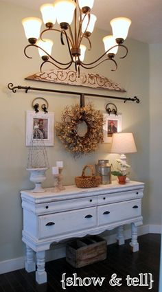 wreath on curtain rod. Nice focal point for the back end of the living room. Recessed lights would be nice above this.
