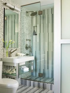 Little Luxuries: Smart solutions can make a small bath seem spacious. In this bath, a space-saving sliding door at the entrance has frosted glass to provide privacy, and running the tile vertically up the shower visually stretches the room. A rain showerhead is a luxurious touch.
