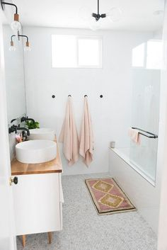 White modern bathroom with wood countertop and pink accessories.