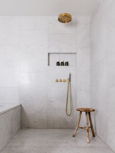 Marble bathroom and three legged wooden stool. Ett Hem Hotel by Studioilse. © Ash James Photography.