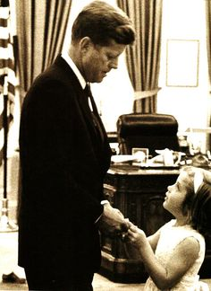 Stanley Tretick took this photograph of Caroline visiting her father in the Oval Office before she went upstairs to school, which her mother started in the White House solarium for the children of the administration officials.