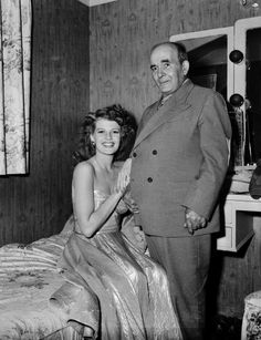 Rita Hayworth, in costume for the film Cover Girl (1944), links arms with her grandfather.