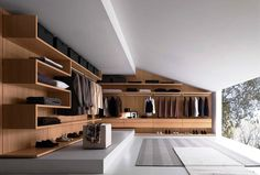Closet and Wardrobe Designs. Modern luxurious open-space grey walk-in closet with stunning wall-mounted wooden wardrobe in cool design with nice grey carpet and beautiful outdoor view. Fancy Dream Home Interior Walk-in Closet Designs