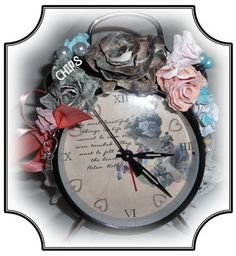 Altered Alarm Clock  Another new item in Donna's collection this sweet  little clock is just darling and as always the detail she put into this little clock can only be shared in person!    Black alarm clock repurposed with handmade water distressed roses and charms. The face was digitally designed.  It includes the quote from Helen Keller – the most beautiful things in life cannot be seen or even touched, they must be felt with the heart.  The time markers on the clock are pink hearts.