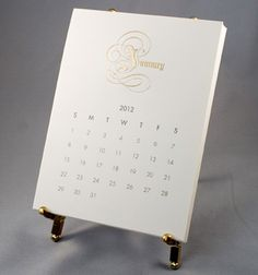 This handsome 2012 Calendar is both luxurious and practical. The names of each month are exquisitely engraved in gold on each 4-ply white card. The Calendar rests on a sturdy brass easel.