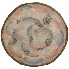 A round second quarter century Art Deco rug having concentric curving pastel bands mirroring the round edges with scattered olive specks in some of the green curves all within a thin brown border. Watch full size video of An Art Deco rug, Circa ID - Video