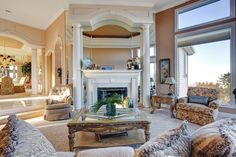Head-on view of fireplace in the prior room, highlighting ornate glass and carved wood coffee table at center.