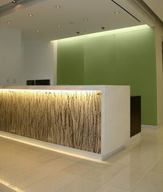 Reception desk with artistic feature, backlit and reflects the effect of the top-lit area behind the desk.