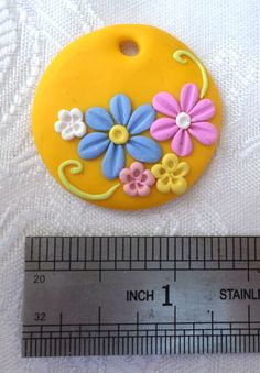 Polymer clay pendant, handmade with applique technique, one of a kind. Yellow, with baby blue, pink, light yellow and white flowers and light apple green swirls. By Lis Shteindel.