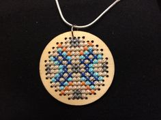 Cross stitched  wooden pendant.