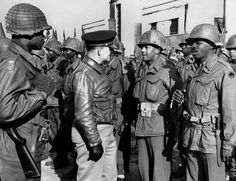 Lt. Gen. Lucian K. Truscott, Jr., commanding general of the Fifth Army in Italy, talks to African American troops of the 92nd Infantry Division after they threw back a German attack in the hills north of Viareggio, Italy in 1944.