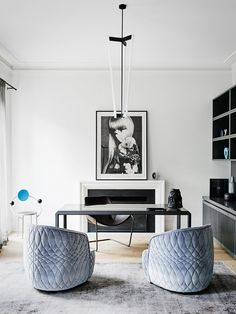Glam monochrome home office space with a large framed photograph, a tube chandelier, and baby blue velvet chairs