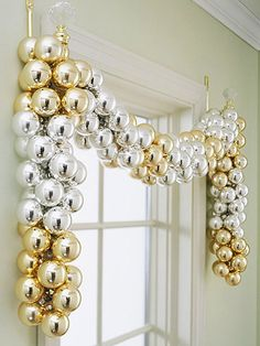 Bands of gold and silver Christmas ornaments drape across this undressed window frame. Attached in clusters with florist's wire to a garland, the ribbon of metallic baubles is suspended from elegant crystal-topped hooks on either side of the window.
