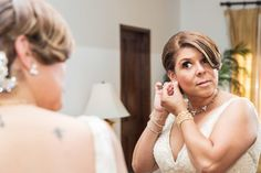 Great Photo of the bride putting on her jewelry! Photography by: Antonio & Paula Crutchley Photography