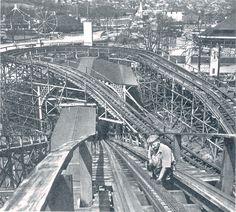 """""""HORSESHOE CURVE. Kennywood's three roller coasters have six miles of track. Every inch must be checked daily in addition to a through reconditioning at the beginning of the season. This workman checks the strength of cable links.""""  Photo and text are copyright of the McKeesport Daily News"""