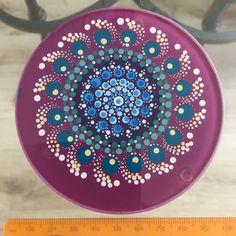 Deze met liefde en zorg gemaakte Mandala Dot Art onderzetter is aan de onderkant van de glasplaat beschilderd met Acrylverven en beschermd met matte vernis plus UV Protectant om verkleuring te voorkomen. Het geheel is waterdicht. Niet vaatwasserbestendig. Het glas is rondom geslepen en de onderzetters zijn aan de onderkant voorzien van rubber nopjes. Doorsnede: 10cm