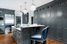 Contemporary kitchen features dark gray cabinets painted Porter Paint Gray Bronze paired with Luce di Luna Quartzite Countertops and a white beveled subway ...