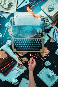 Overhead shot of a typewriter and messy paraphernalia on dark background, an outstretched hand holds a lit match - still life photography ideas.still life photography ideas Hand Photography, Flat Lay Photography, Still Life Photography, Photography Business, Creative Photography, Amazing Photography, Photography Ideas, Artistic Photography, Canon Eos 1300d