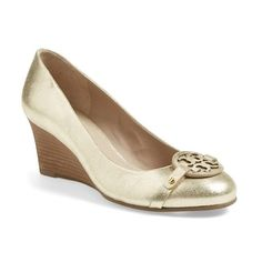 A cutout logo medallion lends an understated signature touch to a round-toe pump cast in pristine metallic leather.  The stacked-wedge heel provides modest hei…