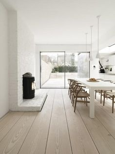 White walls, glass wall/door to garden, bleached wood floor, shadow gap junctions and a wood burner - everything I like!