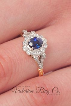 This elegant belle epoque style ring is set with a 1.40 carat oval blue sapphire surrounded by a cluster of 12 round brilliant-cut diamonds. This ring is made with the gemstones set in platinum 950, leading to an 18ct yellow gold band. All rings are made in Hatton Garden to original jewellery designs of their era. #belleepoquejewellery #ovalsapphire #bluesapphireengagementring #mixedmetaljewellery #hattongardenengagementring