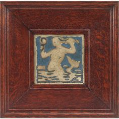 Grueby tile, carved mermaid holding a mirror, gray scene on a blue background, held in an Arts and Crafts oak frame