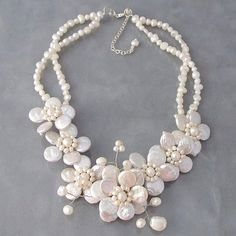This striking necklace is the perfect way to add interest to your wardrobe. This cluster necklace is handmade with pearls and features a beautiful flower detail.