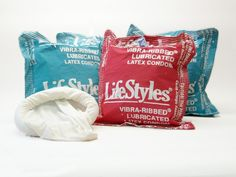 """The giant condom pillow printed with """"Vibra-Ribbed Lubricated Latex Condom"""" measures about 18"""" by 17"""" and is stuffed with polyester filling. There is a large pocket on one side of the pillow that contains an oversized, extra stretchy fabric condom, while a smaller pocket holds actual condoms."""