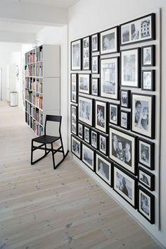 En af ideerne bag indretningen er at tænke i firkanter, da det giver ro. Derfor er billederne på fotovæggen samlet i en firkant, der matcher bogreolens firkant. Også i gangen hænger de lave skabe i firkanter. Rammerne o...