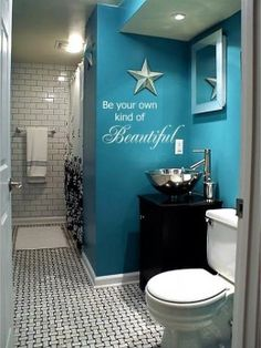 """Beautiful teal bathroom wall with black and white flooring with wall mural stating """"Be Your Own Kind of Beautiful"""""""