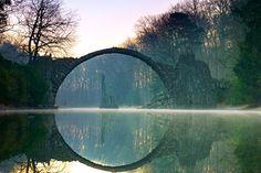 Diese so düster aussehende Brücke ist alles andere als Fantasy. Inoffiziell wird sie 'Teufelsbrücke' genannt. Offiziell heißt sie 'Rakotzbrücke' und steht seit 1860 im Rhododendronpark Kromlau in Sachsen.