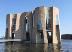 The building rises from the water in the harbour of the city of Vejle. It is accessed across a footbridge, with a subterranean passage also connecting the building's basement to the dockside.