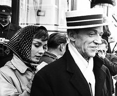 Audrey Hepburn uses Fred Astaire's  back to sign an autograph in Paris