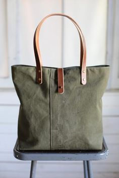 Durable, worn in canvas salvaged from a WWII era US military duffle bag has been thoughtfully reworked into a great every day tote bag.  Fully lined with olive