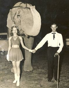 """In the 1950's our elephant act was booked with a Barnes & Carruthers fair unit. We kept the elephants in the race track infield behind the stage.  One morning I awoke to find that the Gene Holter Show had pulled in overnight. They did a matinee and were gone before the dust settled.  During the course of the day, Wally gave my dad this picture of himself, an unidentified lady and """"Gentry Babe""""."""