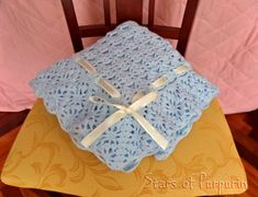 Baby Blanket in blue color with a ornament of satin tie in pale yellow.