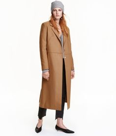 Camel. Long coat in wool-blend fabric with reverse-stitched raw edges. Lapels and concealed snap fasteners at front, seam at waist, and side pockets. Vent