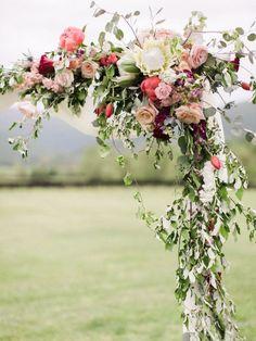 Crimson, magenta, berry, coral, and blush bold wedding flower arch: http://www.stylemepretty.com/virginia-weddings/crozet-virginia/2016/08/12/crimson-charlottesville-wedding/ Photography: Michael & Carina - http://michaelandcarina.com/