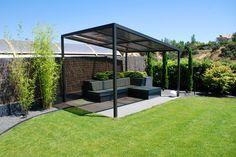 Pergola de hierro lacada en con techo inclinado  de policarbonato. Sofás de obra con jardineras como  respaldo