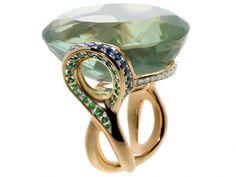 »Eternity Bow« – GREEN BLUE WONDER. Die Unendlichkeitsschlaufe – Lemniskate von Bernoulli – stand Pate für diesen Ring.  Tsavolithe, blaue Saphire und Brillanten blitzen aus den Schlaufen an dem Heliodor (34 x 24mm). Er wird von Stegen mit braunen Brillanten umrundet.