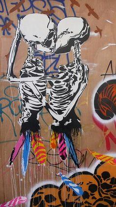 1. Twee kussende skeletten. Wat je niet weet is of het een man en vrouw, vrouw en vrouw, man en man, oud of jong, lichte of donkere huidskleur is. Het zijn twee mensen die de pure vorm van liefde symboliseren. Dit lijkt me een werk van Banksy. Zijn boodschap: gelijkheid. 2 het is mooi uitgewerkt door de witte vorm omlijnt door zwart. De rokjes van veren hebben iets primitiefs, vroeger droegen we allemaal rokjes, dit is een hint naar de levenswijze van primitieve stammen die harmonieus met…