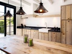 Dark worktops, reclaimed wood and dark lampshades. Giving a modern feel.